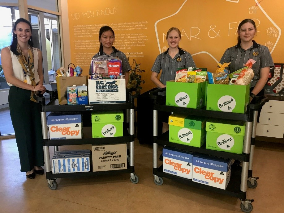 three female Leos and one Leo advisor with boxes of food donations