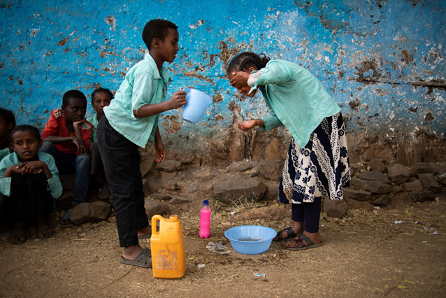 Two children in Gondar Zone, Amhara Region, Ethiopia, wash their faces as part of community-driven trachoma control practices