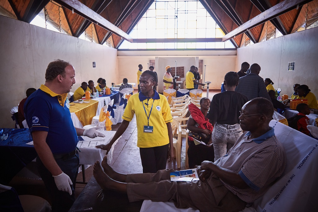 Dr. Fabien Collis, charter member of the Nairobi Phoenix Lions Club, consults with diabetic patient and clinic staff